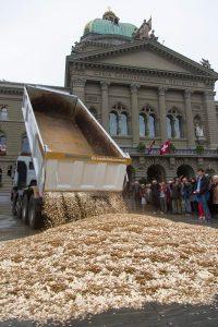 Münzen von einem Lastwagen werden sinnbildlich auf den Bundesplatz geleert. Bild: Keystone/Peter Klaunzer