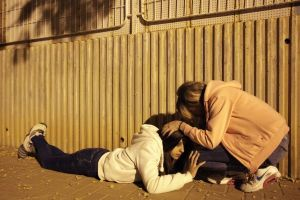 Young Israeli women take coveras a siren sounds warning about incoming rocket fired from Gaza, in the southern Israeli city of Ashkelon,