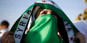 Eine syrische Frau mit den Symbolen der Opposition.  (Bild: reuters)
