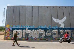 Ein israelischer Soldat geht an einem kunstvoll bemalten Schutzwall gegen Raketen vorbei, gesehen im Kibbuz Netiva Haasara im Süden Israels.